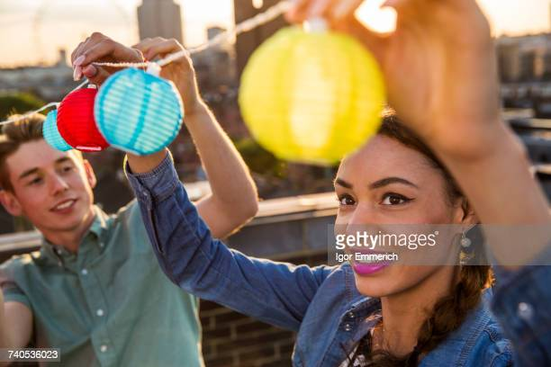 Young man and woman hanging lights at roof party in London, UK