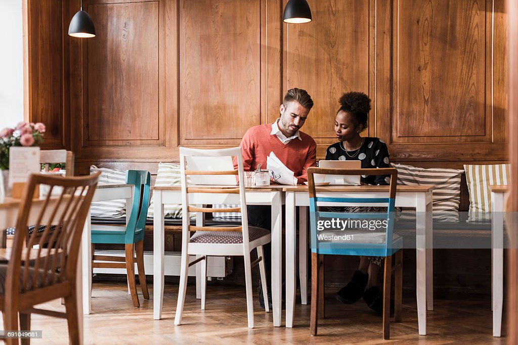 Young man and woman having a meeting in a cafe : Stock Photo