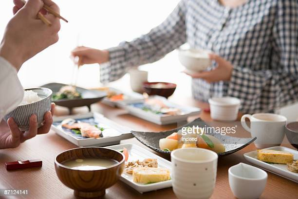 Young man and woman having breakfast on table