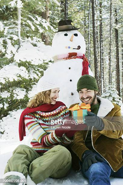 Young man and woman holding gift in front of snowman, smiling