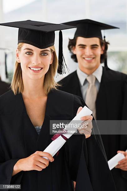 YOung man and woman holding graduation certificates