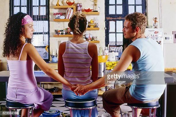 young man and woman holding hands behind the back of another woman - romantiek begrippen stockfoto's en -beelden