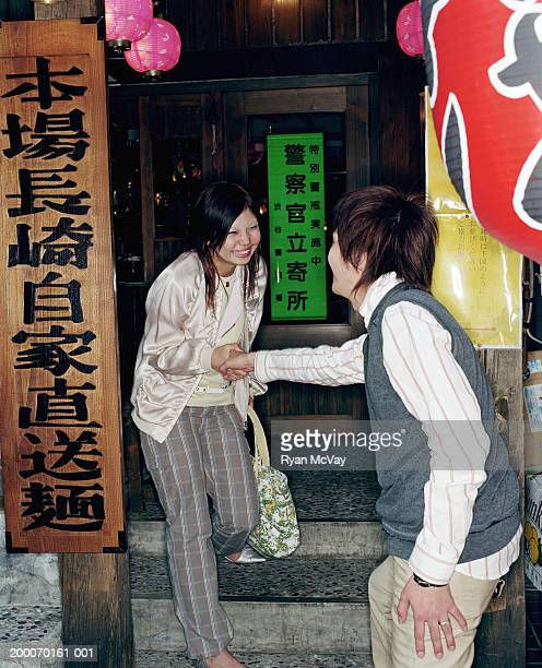 Young man and woman holding hands in front of restaurant, smiling