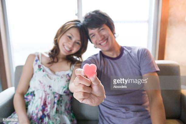 Young man and woman holding heart shaped candy, smiling