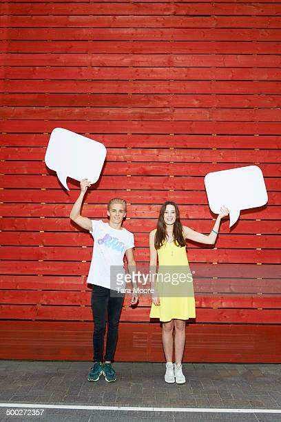 young man and woman holding up speech bubbles