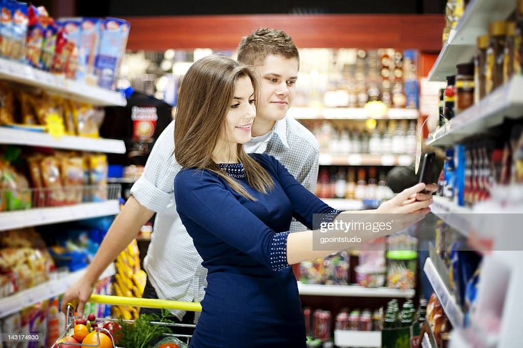 Young man and woman in a grocery store : Stock Photo