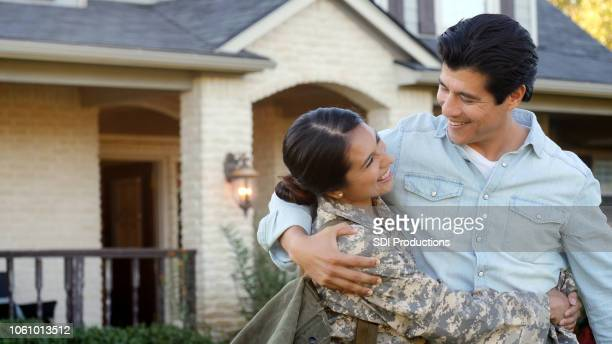 young man and woman in a uniform look at each other smiling - military spouse stock pictures, royalty-free photos & images