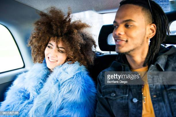 young man and woman in back of taxi, smiling - winter coat stock pictures, royalty-free photos & images
