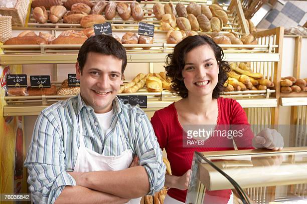 Young man and woman in bakery, smiling, portrait