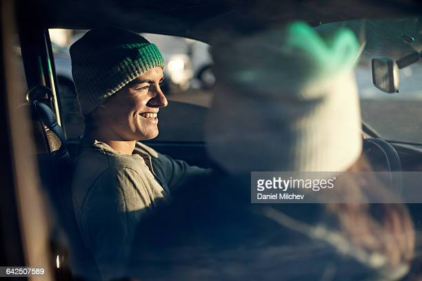 Young man and woman in car, man smiling