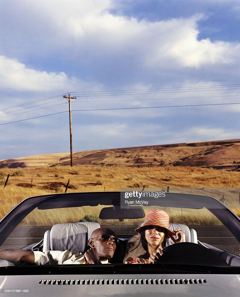 Junger Mann und Frau im Cabrio Auto : Stock-Foto