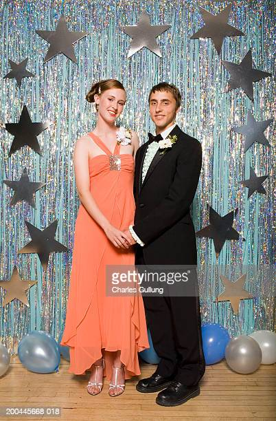 Young man and woman in formalwear holding hands, portrait