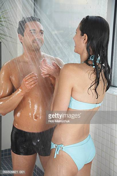 young man and woman in swimsuits showering at spa - couples showering together stock photos and pictures