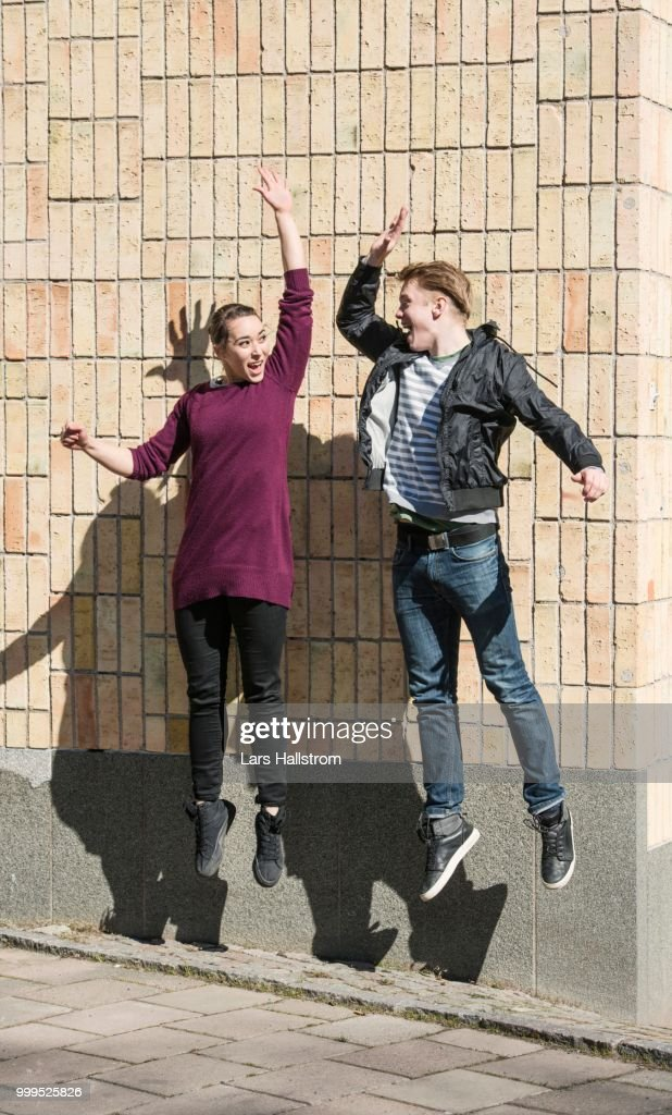 Young man and woman jumping and doing a high five greeting sweden young man and woman jumping and doing a high five greeting sweden stock photo m4hsunfo