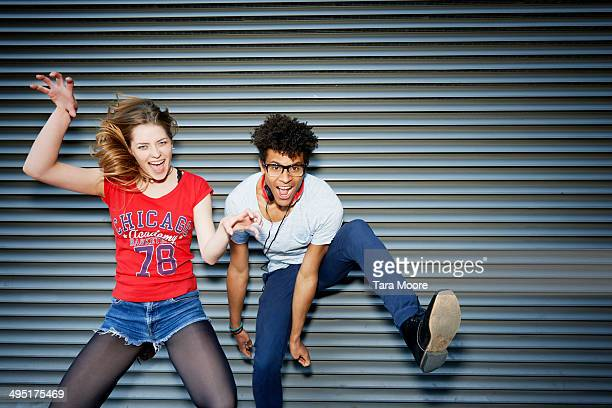 young man and woman jumping having fun - 25 29 anos imagens e fotografias de stock