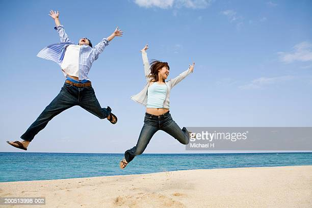 young man and woman jumping in midair on beach, arms raised - legs apart stock pictures, royalty-free photos & images