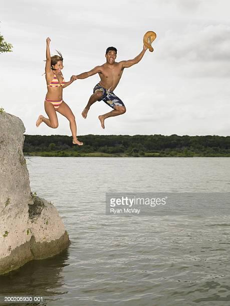 若い男性と女性の出発湖、岩を保持