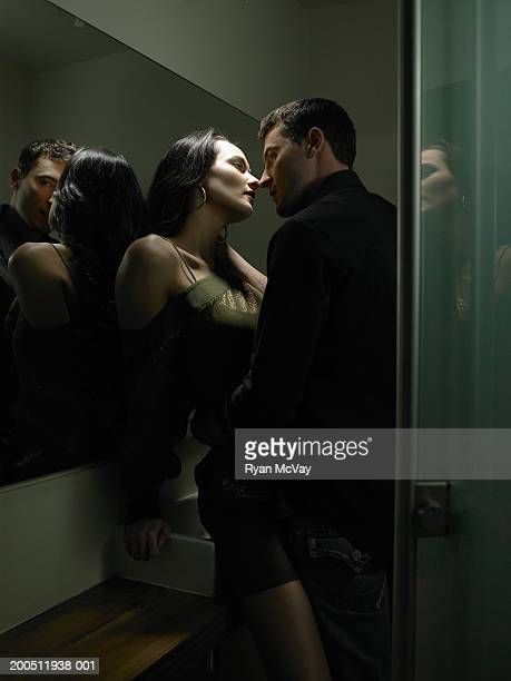 Young man and woman kissing in public restroom, side view