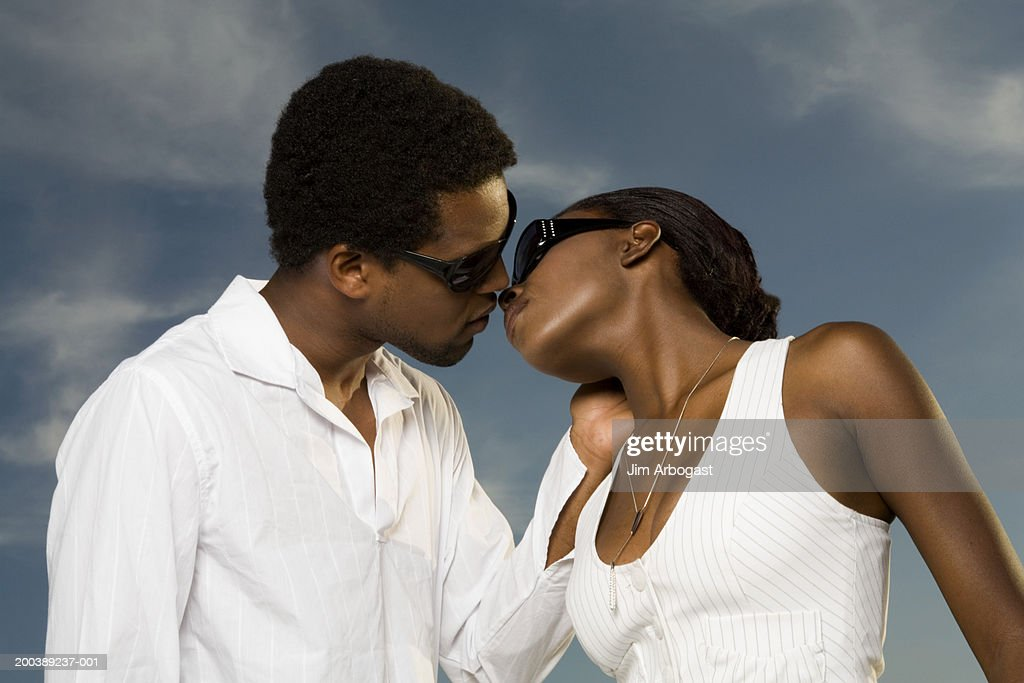 Young man and woman kissing, side view : Stock Photo