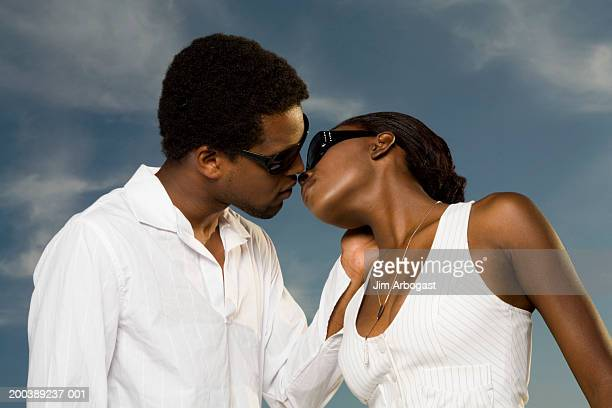 young man and woman kissing, side view - chest kissing stock pictures, royalty-free photos & images