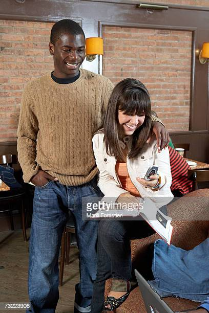 Young man and woman looking at mobile phone, smiling, close-up