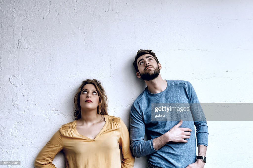 young man and woman looking up in the air : Stock Photo