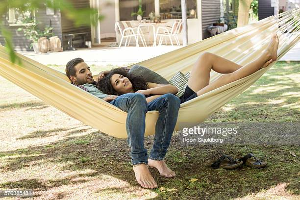 young man and woman lying in hammock smiling - robin skjoldborg stock pictures, royalty-free photos & images