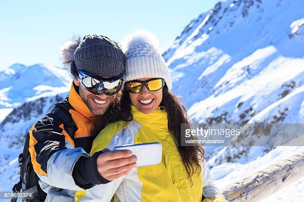 Young man and woman making selfie on snow mountain