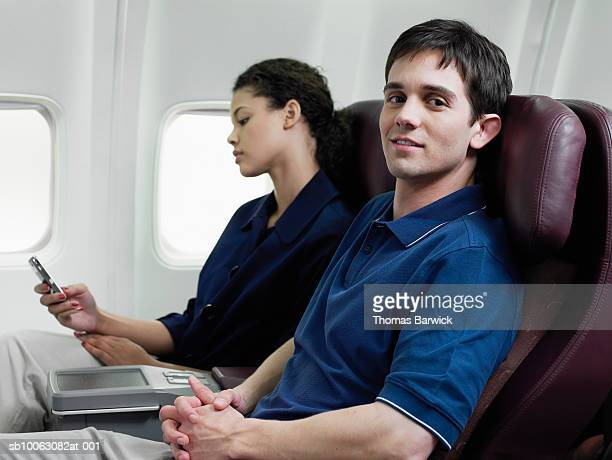 Young man and woman on airplane, man looking at camera