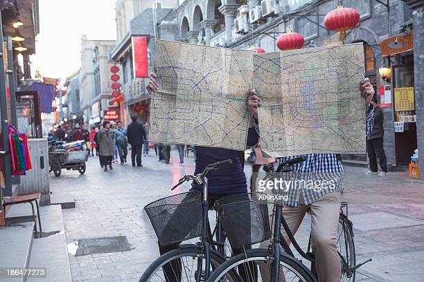 Young man and woman on bicycles holding maps.