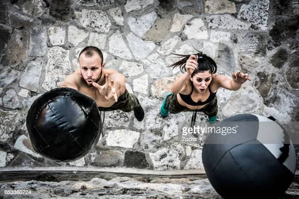 young man and woman on cross training throwing medicine ball - medicine ball stock pictures, royalty-free photos & images