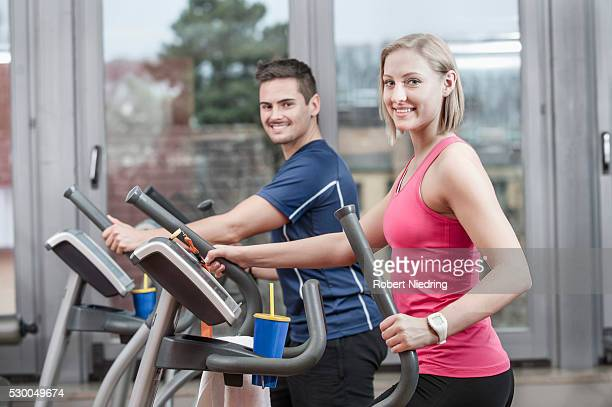 Young man and woman on elliptical trainer in gym