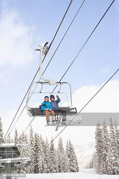 Young man and woman on ski lift, low angle view