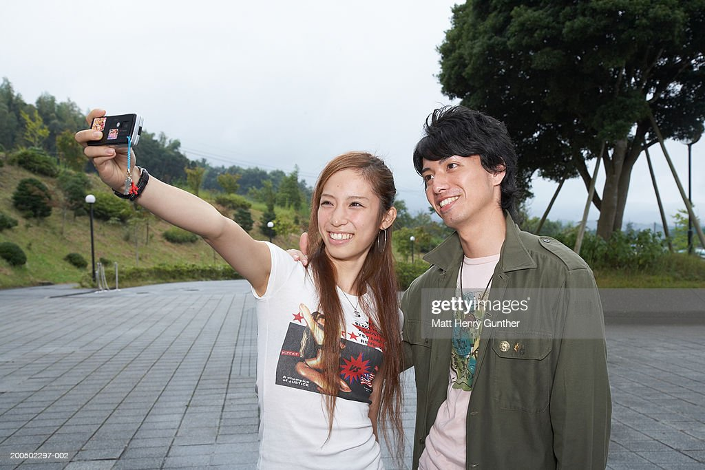Young man and woman photographing themselves with camera phone : Stockfoto