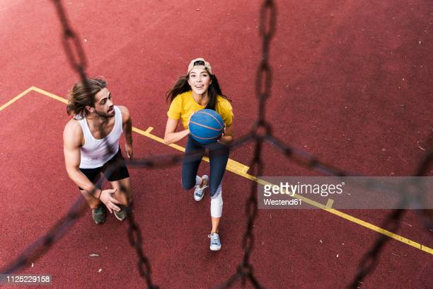 young man and woman playing basketball on basketball ground - drive ball sports stock pictures, royalty-free photos & images