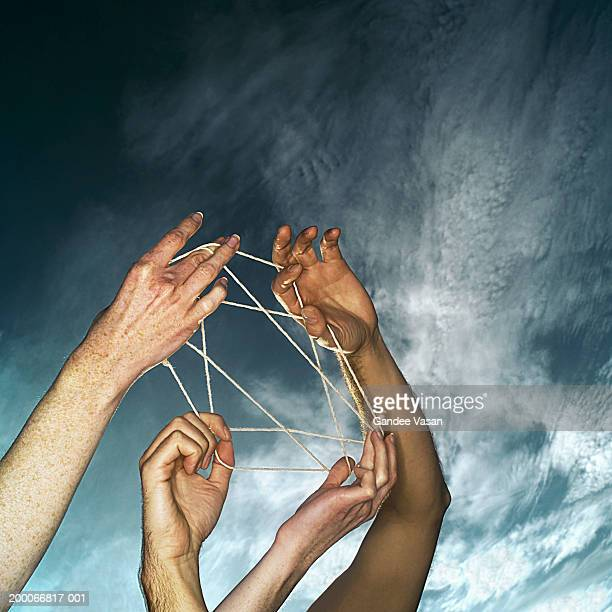 Young man and woman playing cat's cradle, low angle view, close-up