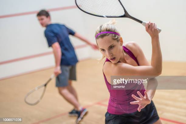 young man and woman playing squash game - squash sport stock pictures, royalty-free photos & images