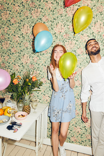 Young man and woman playing with balloons while standing against wallpaper at home during dinner party - gettyimageskorea