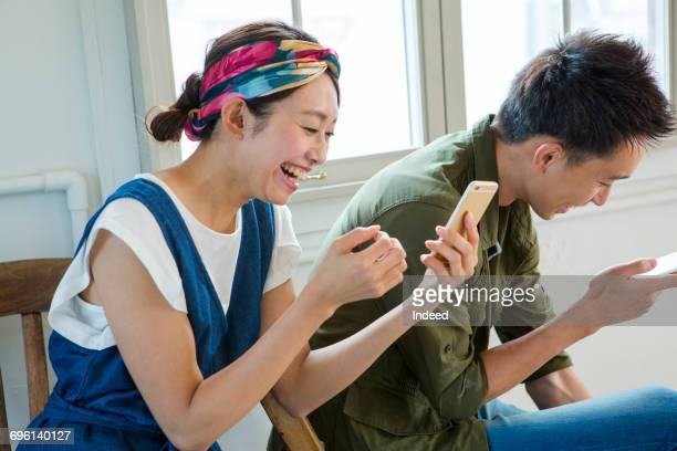 Young man and woman playing with smart phone, smiling