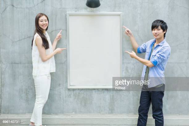 Young man and woman pointing at blank board