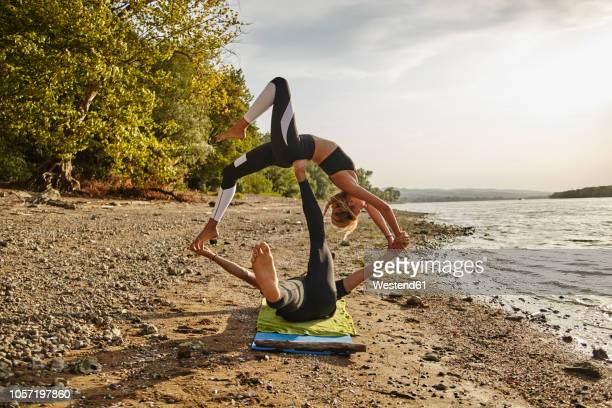 Young man and woman practicing Acro Yoga