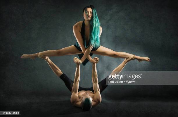 young man and woman practicing acrobat against gray background - aikāne stock pictures, royalty-free photos & images