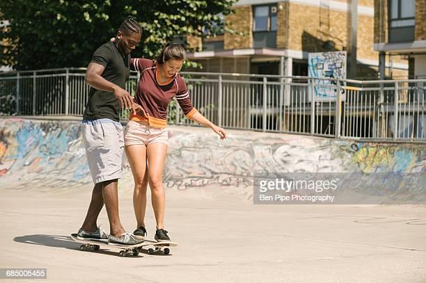 young man and woman practising skateboarding balance in skatepark - participacion ciudadana fotografías e imágenes de stock