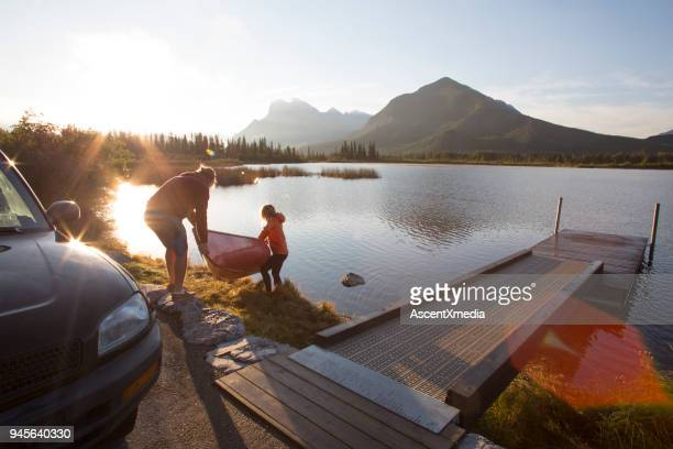 young man and woman prepare canoe for lake ride, in mountains - maroon stock pictures, royalty-free photos & images