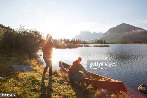 young man and woman prepare canoe for lake ride, in mountains - banff national park stock pictures, royalty-free photos & images