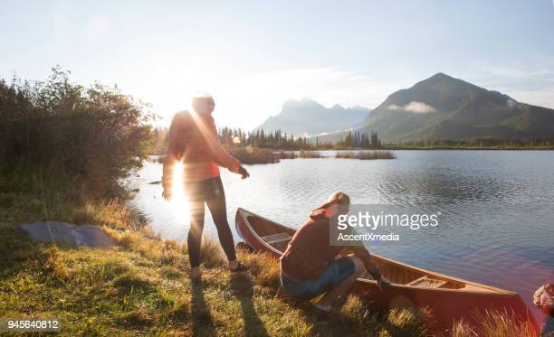 young man and woman prepare canoe for lake ride, in mountains - banff stock photos and pictures