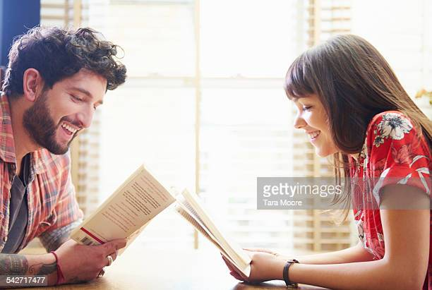 young man and woman reading books at home - beautiful people stock pictures, royalty-free photos & images