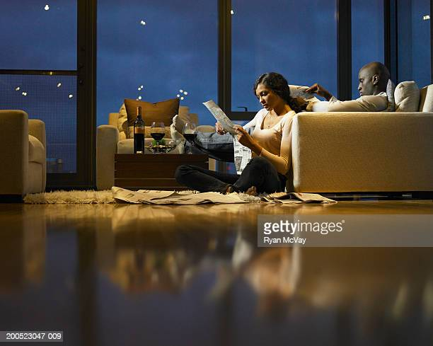 Young man and woman reading newspaper in living room, dusk, side view