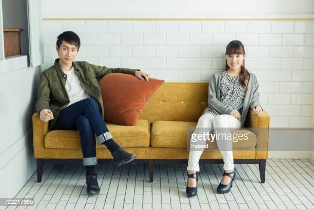 young man and woman relaxing on sofa - side by side stock photos and pictures