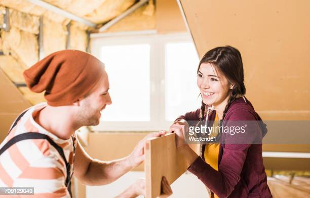 Young man and woman renovating their new home, holding a plank